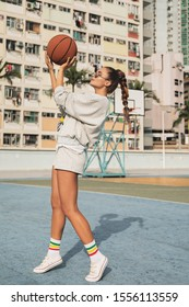 Young stylish woman  is posing on the Choi Hung Estate Basketball Court in Hong Kong city