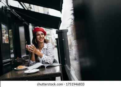 Young stylish woman in red beret having a french breakfast with coffee sitting oudoors at the cafe terrace.