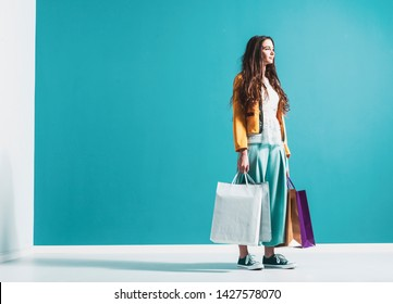 Young stylish woman with shopping bags, she is looking away and smiling, sales and fashion concept