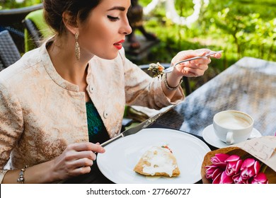 young stylish woman sitting in cafe, eating tasty pie, enjoying healthy food, cappuccino, tulips, happy birthday party, city street, boho outfit, europe vacation, fashion, romantic dinner, open mouth