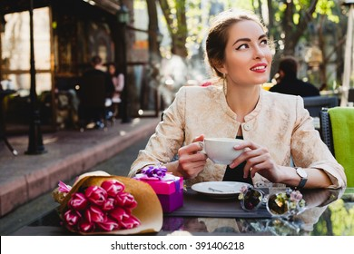 young stylish woman, sitting in cafe, holding drinking cup cappuccino, smiling, tulips, happy birthday party, city street, europe vacation, glamour outfit, romantic dinner, thinking, dreaming