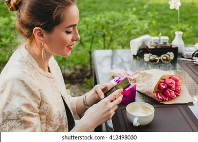 young stylish woman sitting in cafe, holding smart phone, drinking cup cappuccino, enjoying, tulips, celebrating party, city street, boho outfit, europe vacation, romantic dinner, smiling, presents
