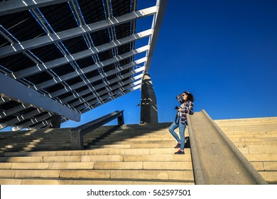 Young and stylish woman is standing on stairs next to the huge solar panel in industrial park on sunny day, Barcelona, Spain