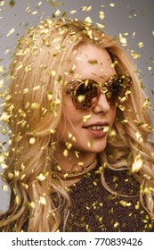 Young stylish woman in sunglasses posing contently in flying golden confetti looking away.