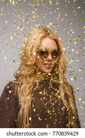 Young stylish woman in sweater and sunglasses posing confidently in flying golden glitters.