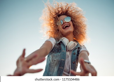 Young stylish woman with very lush hair makes a friendly gesture. Young woman with big headphones. outdoors portrait of a trendy girl