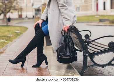 young stylish woman walking in autumn city, cold season, wearing high heeled black boots, leather backpack, accessories, grey coat, sitting on bench, fashion trend, legs close-up details
