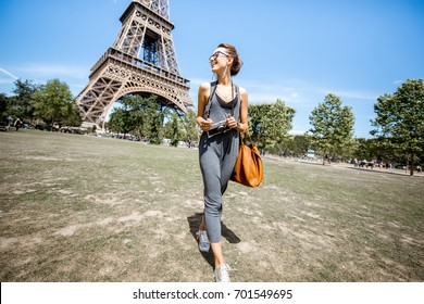 Young stylish woman walking with bag and photo camera in front of the Eiffel tower in Paris
