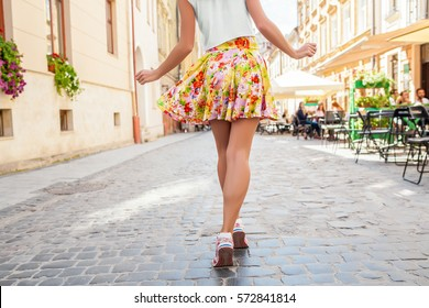 young stylish woman walking the city street in summer, colorful skirt, fashion trend, legs