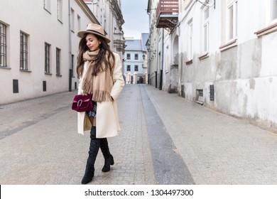 Young stylish woman walking on the street. Wearing stylish bright coat and skirt.