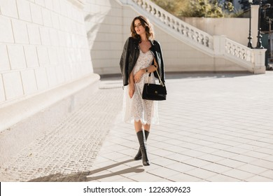 young stylish woman walking in street in fashionable outfit, holding purse, wearing black leather jacket and white lace dress, spring autumn style, posing, high leather boots