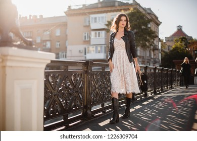 young stylish woman walking in street in fashionable outfit, holding purse, wearing black leather jacket and white lace dress, spring autumn style, high boots, warm sunny weather, romantic look