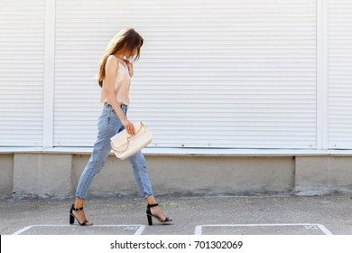 Young stylish woman wearing beige cami silk top, blue cropped denim jeans, black high heel sandals and holding clutch bag walking in the city street. Trendy casual outfit. Street fashion. In motion.