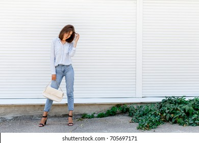 Young stylish woman wearing blue striped shirt, blue cropped denim jeans, black high heel sandals and beige handbag posing outdoors against white street wall. Trendy casual outfit. Street fashion.