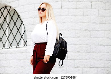 Young stylish woman wearing neutral blazer and hat walking on the city street in spring. Casual fashion, elegant look. Plus size model.
