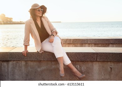 Young stylish woman wearing neutral blazer and hat walking on the city street at the afternoon. Casual fashion, elegant look. Plus size model.