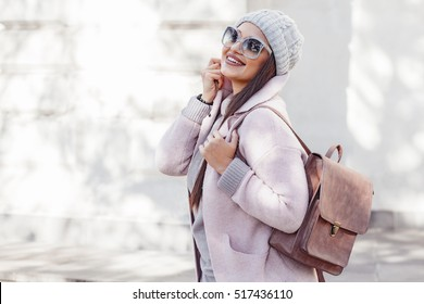 Young stylish woman wearing pink warm coat, pants and handbag walking in the city street in cold season. Winter fashion, elegant look, outfit in pastel colors. Plus size model.