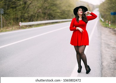 Young stylish woman wearing red dress, black hat walking on the city street in autumn/spring. Fall fashion, elegant look. Plus size model.