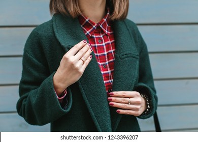 Young stylish woman wearing red plaid shirt and green coat standing near blue wooden wall on the city street. Trendy casual outfit. Details of everyday look. Street fashion. No face.