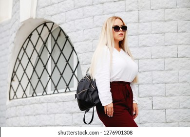 Young stylish woman wearing white blouse and burgundy color pants, black real leather backpack walking on the city street in spring. Casual fashion, elegant look. Plus size model.