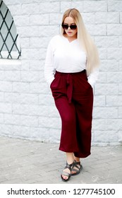 Young stylish woman wearing white blouse and burgundy color pants walking on the city street in spring. Casual fashion, elegant look. Plus size model.