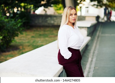 Young stylish woman wearing white blouse and burgundy color pants walking on the city street in autumn. Casual fashion, elegant look. Plus size model. Fall fashion