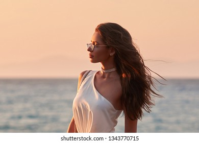 Young stylish woman in white blouse, trousers and sunglasses standing at sea coast and enjoying tropical sunset. Elegant rich girl looking away
