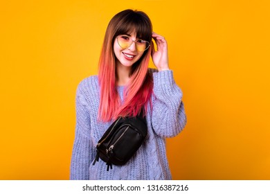 Young stylish wonderful hipster woman with long ombre fuchsia hairs posing at studio yellow background, spring vibes, soft pastel colors, vintage hearted sunglasses and trendy bum bag.