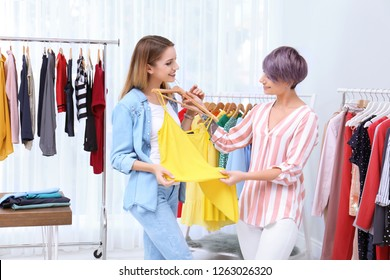 Young stylist helping customer to choose clothes indoors