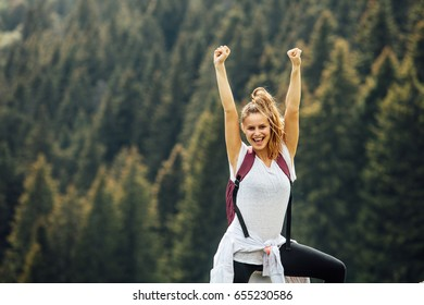 young and succesfull woman standing on top of the mountains happy for her achievement