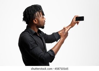 Young successful african businessman making selfie over white background.