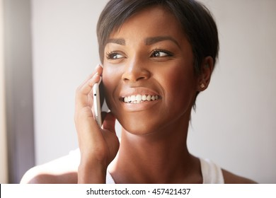 Young successful African fitness instructor receiving grateful call from her trainee at fitness center, looking happy and cheerful talking on the phone, smiling. People and technology concept