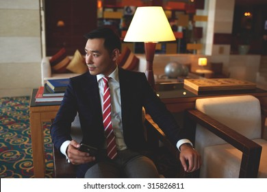 Young successful asian businessman dressed in formal wear holding mobile phone while sitting in modern office,confident rich men entrepreneur waiting for a call on his cell telephone during work break