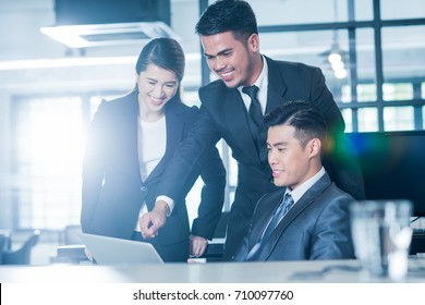 Young and successful Asian businesspeople at work. Image with lens flare effect.