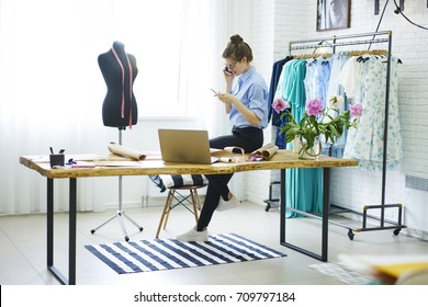 Young successful atelier owner in spectacles having mobile conversation in positive atmosphere on smartphone while standing in studio.Talented female designer talking on telephone during work indoors