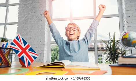 Young successful boy raises hands up while learning english in light classroom