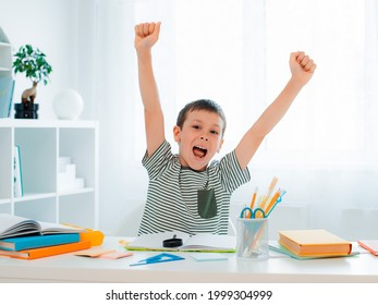 Young successful boy raises hands up when I finished my homework, triumphant exclamation, solved the problem, victory, finish, the joy of learning - Shutterstock ID 1999304999