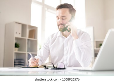 Young successful broker consulting client by smartphone while making working notes in notebook by desk