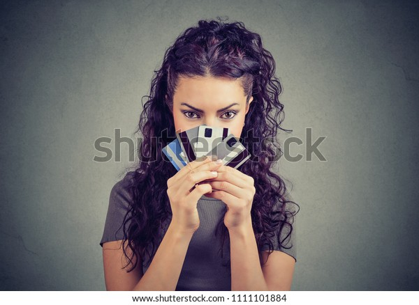 Young successful brunette having many credit cards looking cunning at camera and spending money