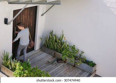 Young successful business man busy locking his front door after arriving at his beach house