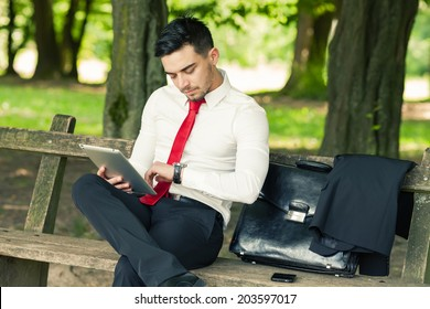 Young and successful business man sitting on the park bench holding a tablet and checking time