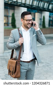 Young successful business man talking on phone and explaining something wearing suit and glasses.