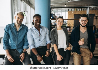 Young and successful business team. People in smart casual wear looking at camera and smiling while standing in their creative office