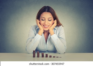 Young successful business woman sitting at table looking at growing stack of coins. Financial freedom target success concept