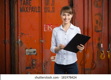 Young successful business woman is standing near the containers and manages the logistics process