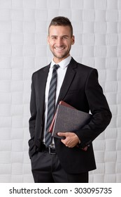 Young successful businessman big laughing and keeping his hand in pocket. Short-haired man in business suit carrying two registers.
