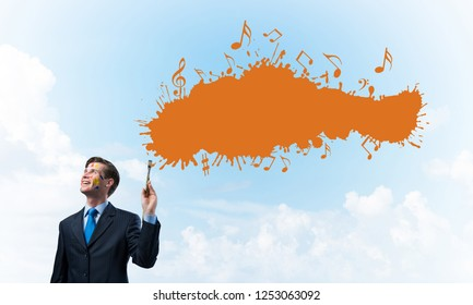 Young and successful businessman in black suit holding paintbrush in hand and smiling while standing with orange liquid splash with against cloudy skyscape view on background.