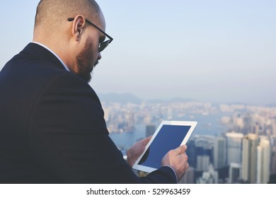 Young successful businessman checking banking accounts in upgrade application for touch pad with mock up screen using wifi connection on cityscape background. Copy space area for advertising content