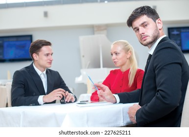 Young successful businessman confidently looks at the camera while sitting at the table with partners. Business pair girl and man are sitting on the background and discussing business projects