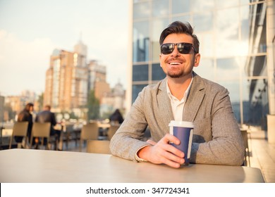 Young successful businessman drinking coffee in the office center